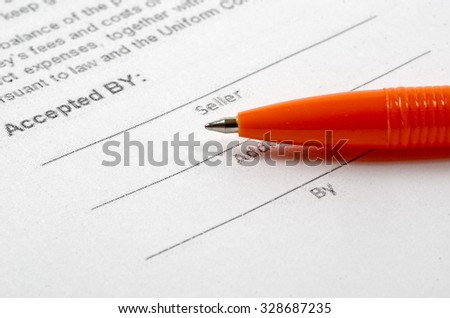 the sales agreement form lies on a table. On it the pen lies - stock photo