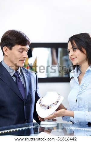 The saleswoman and the businessman in jeweller shop - stock photo