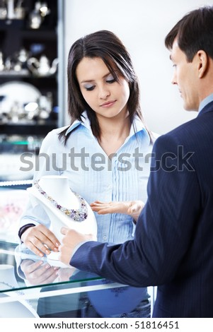 The saleswoman shows a necklace to the man in shop - stock photo