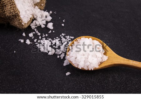 the salt crystals on black stone plate background , selective focus - stock photo