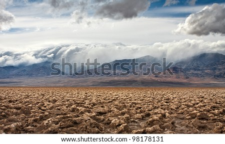The salt formations at Devils Golf Course in Death Valley National Park.  A storm rolls in over the mountains in the distance. - stock photo