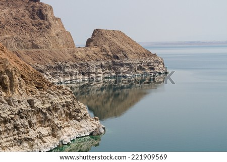 The salty shore of the Dead Sea on the Jordan side, with salt formations. - stock photo