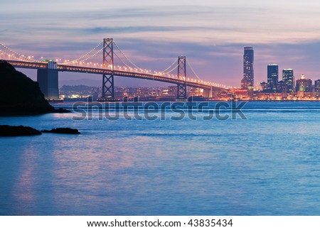 The San Francisco-Oakland Bay Bridge at dusk with Yerba Buena Island in the foreground and San Francisco's Rincon Hill in the background - stock photo