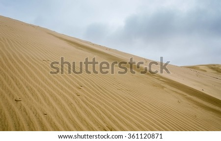 The sand hill is under the cloudy sky - stock photo