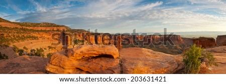 The sandstone red rock of Colorado National Monument glows under a sunrise. - stock photo