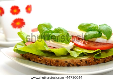 The sandwich of lettuce, the tomato, Camembert cheese and with fresh basil.
