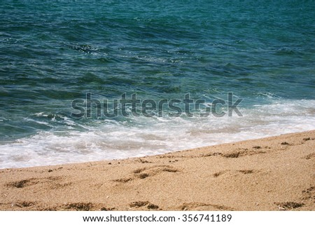 The sandy beach and the sea with white foam on a hot summer sunny warm day - stock photo