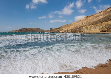 The sandy beach below the rocky cliffs of the Malta island
