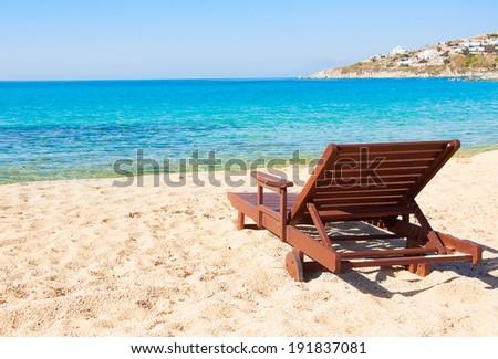 The sandy beach near the blue sea with sun beds. Mykonos - stock photo