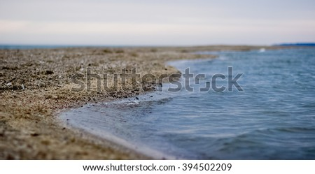 The sandy seashore with pebble, a twisting bend of an edge of water and turquoise water of the Black Sea. - stock photo