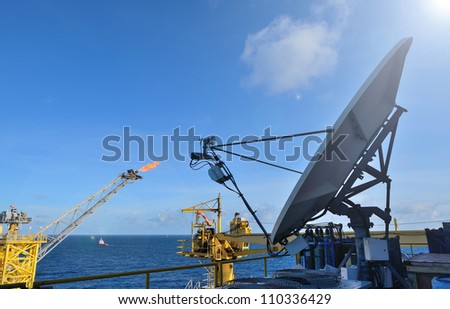 The satellite dish is set on the offshore oil rig platform in the gulf of thailand. - stock photo