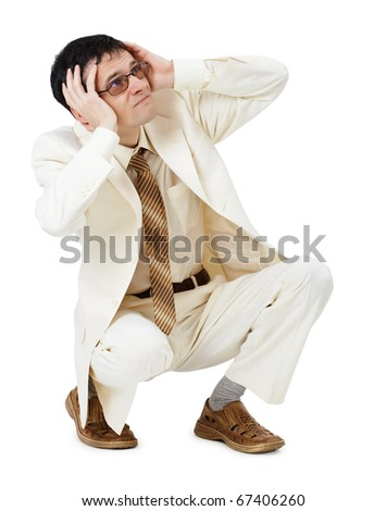 The scared young man in a white suit sits - stock photo