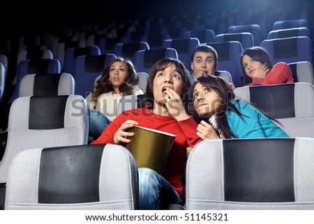 The scared young people at cinema viewing - stock photo
