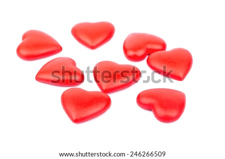 The scattered red heart made of plastic on a white