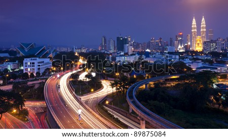 The scenario of Kuala Lumpur city, taken with slow shutter speed to get the light trail from the highway traffic. Stunning light trail at highway in Kuala Lumpur city - stock photo