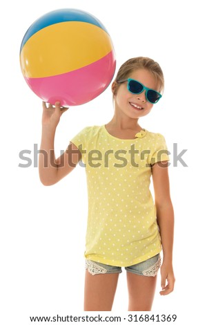 The school age girl in sunglasses , shorts and a yellow t-shirt with short sleeves holding the ball. Girl playing volleyball with their peers on the beach-Isolated on white background - stock photo