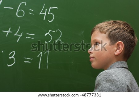 The schoolboy at a lesson of mathematics at a school board - stock photo