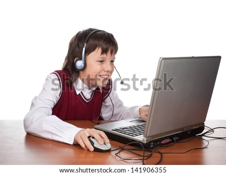The schoolboy plays a laptop in a computer game  - stock photo