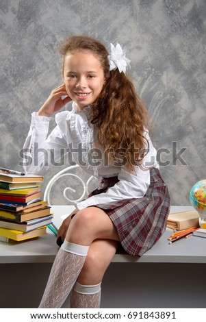The schoolgirl in school uniform sits on the desk and smiles happily on a light gray background. Back to school. The new school year. Child education concept.