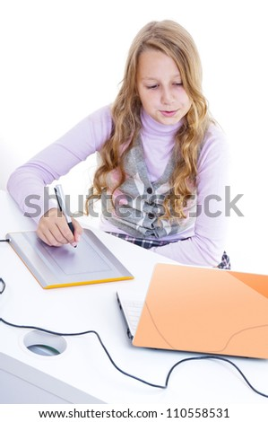 The schoolgirl painting with the digitizer and netbook - stock photo