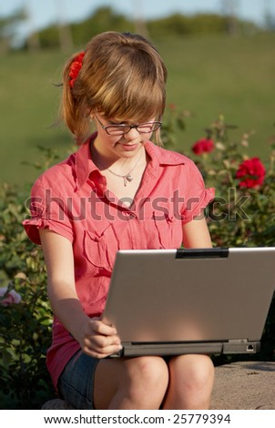 The schoolgirl with laptop in park - stock photo