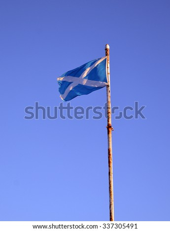 The Scottish saltire flag flies on a rusty flagpole at Torry Battery, Aberdeen, Scotland
