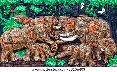 The Sculpture of family elephant on wall - stock photo