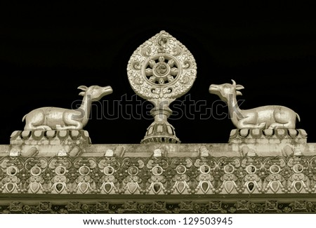 The sculpture of the wheel of Dharma and two deer on the roof of the gate of the Tengboche monastery - Nepal, Himalayas (stylized retro) - stock photo