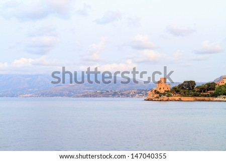 The Sea at Bagheria in the evening in Sicily near Palermo, Italy. View on a medieval Fortress on the blue sea