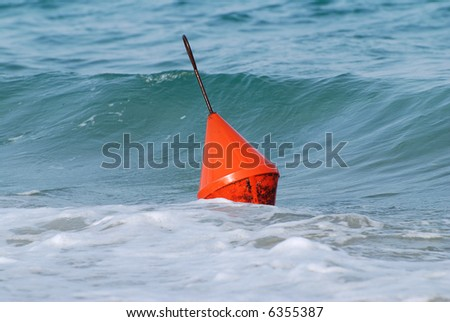 The sea is playing with the orange buoy - stock photo