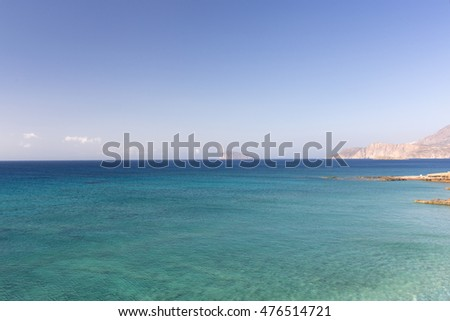 The sea of different colors of blue surrounded by mountains