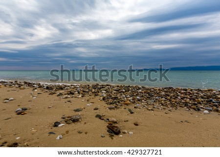 The sea shore, the calm sea, sand and pebbles on the beach. The sky is full with interesting clouds.