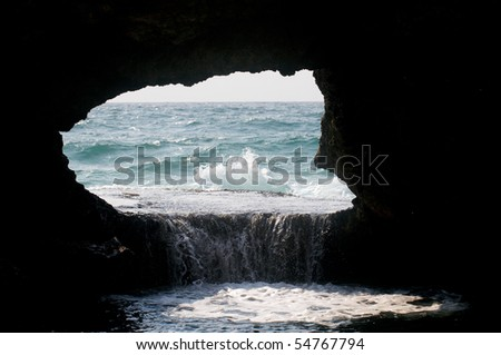 The Sea washing into hole in the rock - stock photo