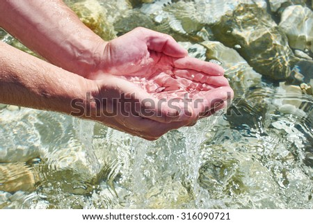 The sea water in the palms of man - stock photo