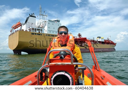 The seaman operates a rescue boat during man overboard drill - stock photo
