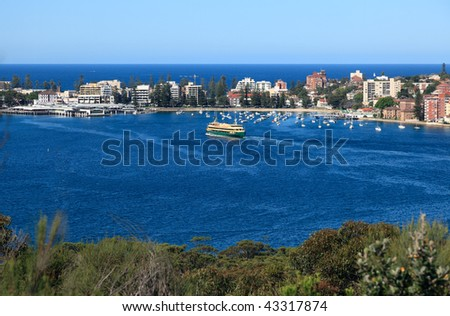 The seaside suburb of Manly from the Sydney Harbour National Park. The Ferry can be seen pulling into port. - stock photo