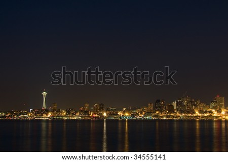 The Seattle, Washington skyline at night with Puget Sound in the foreground, with lots of sky copyspace. - stock photo