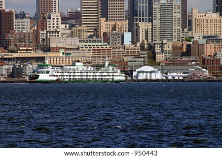The Seattle Waterfront with a ferry in the foreground. - stock photo