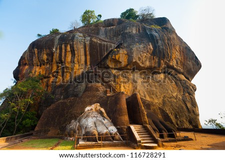 The second level stairs and entrance to the former fortress and monastery of Sigiriya rock, guarded by a pair of lion feet in Sri Lanka - stock photo