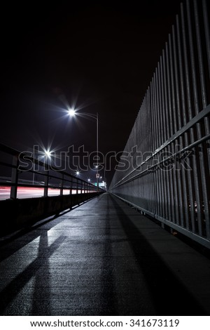The Second Narrows Bridge sidewalk at night, with light trails from passing cars.  - stock photo