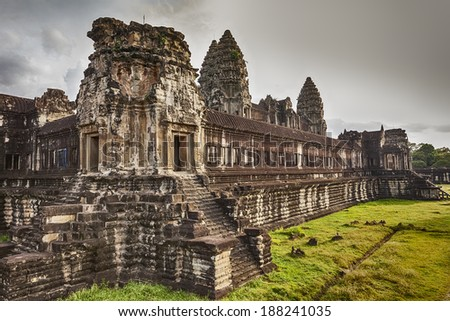 The second of three courtyard walls of Angkor Wat showcases the ancient Khmer architecture. Three of the central towers are visible over the walls. - stock photo