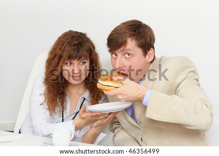 The secretary is feeding his boss at workplace - stock photo