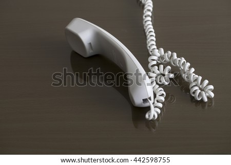 The selective focus close up image of white phone hanging Isolated on black table. Busy concept - stock photo