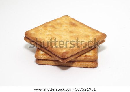 the selective focus of the cream cracker biscuits on white background. the cream cracker tag on the biscuit.  - stock photo