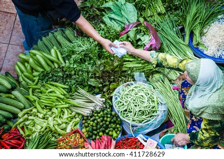 The seller gives the money to the buyer at the vegetable market - stock photo