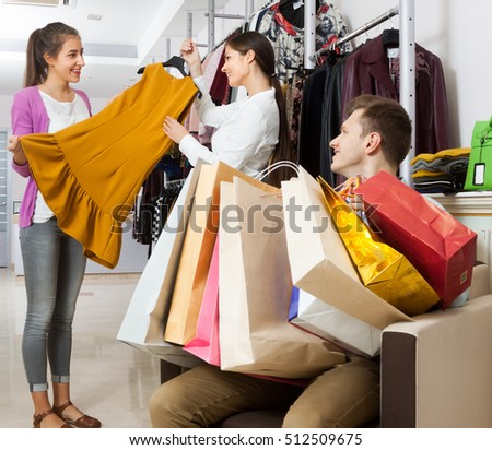 The seller in a clothing store offers young woman dress. A man waits for her sitting in a chair