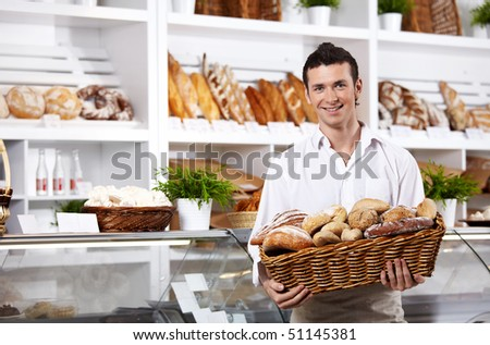 The seller in shop holds a basket with rolls