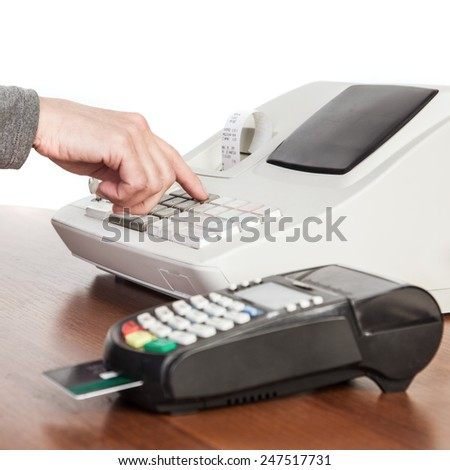 The seller makes the calculation and takes payment by a cash register and credit card reader. - stock photo