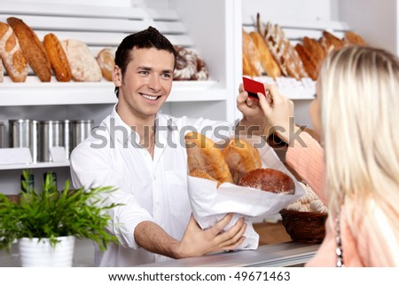 The seller sells to the girl bread in a bakery - stock photo