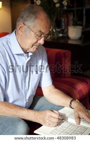 The senior man doing sudoko at home. - stock photo